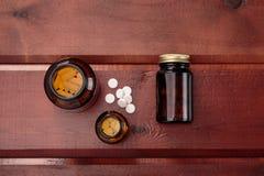 Σωρός των άσπρων χαπιών και των μπουκαλιών γυαλιού για τα φάρμακα Τοπ όψη Στοκ εικόνα με δικαίωμα ελεύθερης χρήσης