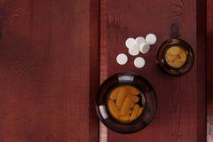 Σωρός των άσπρων χαπιών και των μπουκαλιών γυαλιού για τα φάρμακα Τοπ όψη Στοκ Φωτογραφίες