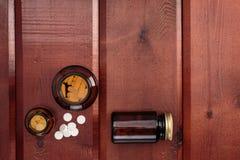 Σωρός των άσπρων χαπιών και των μπουκαλιών γυαλιού για τα φάρμακα Τοπ όψη Στοκ Εικόνες
