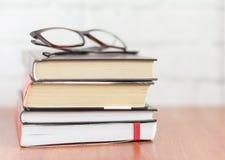 Σωρός των βιβλίων και των γυαλιών στον πίνακα, μυθιστοριογραφία για την ανάγνωση στοκ φωτογραφία με δικαίωμα ελεύθερης χρήσης