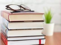 Σωρός των βιβλίων και των γυαλιών στον πίνακα, μυθιστοριογραφία για την ανάγνωση στοκ εικόνα