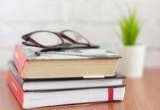 Σωρός των βιβλίων και των γυαλιών στον πίνακα, μυθιστοριογραφία για την ανάγνωση στοκ φωτογραφίες