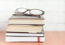 Σωρός των βιβλίων και των γυαλιών στον πίνακα, μυθιστοριογραφία για την ανάγνωση στοκ εικόνες