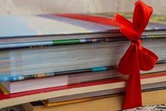 Σωρός των βιβλίων με τις σκληρές και καλύψεις εγγράφου που δένονται από την κόκκινη κορδέλλα ως α Στοκ εικόνες με δικαίωμα ελεύθερης χρήσης