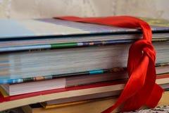 Σωρός των βιβλίων με τις σκληρές και καλύψεις εγγράφου που δένονται από την κόκκινη κορδέλλα ως α Στοκ φωτογραφίες με δικαίωμα ελεύθερης χρήσης