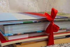 Σωρός των βιβλίων με τις σκληρές και καλύψεις εγγράφου που δένονται από την κόκκινη κορδέλλα ως α Στοκ φωτογραφία με δικαίωμα ελεύθερης χρήσης