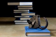 Σωρός των βιβλίων που διαβάζουν σε έναν ξύλινο πίνακα Εκτός από τα ψέματα και το λουκέτο Στοκ φωτογραφία με δικαίωμα ελεύθερης χρήσης