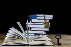 Σωρός των βιβλίων που διαβάζουν σε έναν ξύλινο πίνακα Εκτός από τα ψέματα και το ρολόι Στοκ φωτογραφίες με δικαίωμα ελεύθερης χρήσης