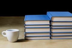 Σωρός των βιβλίων που διαβάζουν σε έναν ξύλινο πίνακα Εκτός από τα ψέματα και το φλυτζάνι Στοκ φωτογραφία με δικαίωμα ελεύθερης χρήσης