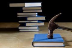 Σωρός των βιβλίων που διαβάζουν σε έναν ξύλινο πίνακα Εκτός από τα ψέματα και το σφυρί Στοκ Εικόνα