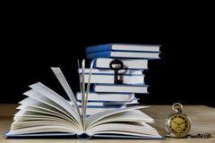 Σωρός των βιβλίων που διαβάζουν σε έναν ξύλινο πίνακα Εκτός από τα ψέματα και το κλειδί BL Στοκ Φωτογραφίες