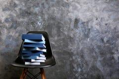 Σωρός των βιβλίων στην καρέκλα ενάντια σε γκρίζο Στοκ φωτογραφία με δικαίωμα ελεύθερης χρήσης