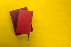 Σωρός των βιβλίων βιβλίων με σκληρό εξώφυλλο, του ημερολογίου στον ξύλινο πίνακα γεφυρών και του κίτρινου υποβάθρου πίσω σχολείο  Στοκ εικόνα με δικαίωμα ελεύθερης χρήσης