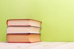 Σωρός των βιβλίων βιβλίων με σκληρό εξώφυλλο, του ημερολογίου στον ξύλινο πίνακα γεφυρών και του πράσινου υποβάθρου πίσω σχολείο  Στοκ Εικόνα