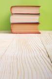 Σωρός των βιβλίων βιβλίων με σκληρό εξώφυλλο, του ημερολογίου στον ξύλινο πίνακα γεφυρών και του πράσινου υποβάθρου πίσω σχολείο  Στοκ φωτογραφίες με δικαίωμα ελεύθερης χρήσης