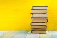 Σωρός των βιβλίων βιβλίων με σκληρό εξώφυλλο, του ημερολογίου στον ξύλινο πίνακα γεφυρών και του κίτρινου υποβάθρου πίσω σχολείο  Στοκ εικόνες με δικαίωμα ελεύθερης χρήσης