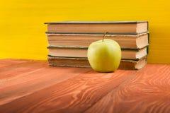 Σωρός των βιβλίων βιβλίων με σκληρό εξώφυλλο, του ημερολογίου στον ξύλινο πίνακα γεφυρών και του κίτρινου υποβάθρου πίσω σχολείο  Στοκ φωτογραφίες με δικαίωμα ελεύθερης χρήσης