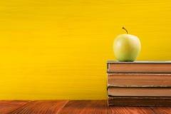 Σωρός των βιβλίων βιβλίων με σκληρό εξώφυλλο, του ημερολογίου στον ξύλινο πίνακα γεφυρών και του κίτρινου υποβάθρου πίσω σχολείο  Στοκ Φωτογραφίες