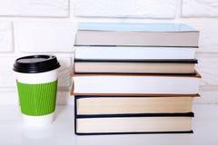 Σωρός των βιβλίων και ένα φλιτζάνι του καφέ στο γραφείο Διαστημική και εκλεκτική εστίαση αντιγράφων Στοκ Εικόνα