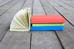 Σωρός των βιβλίων και του ανοικτού βιβλίου με τις αερισμένες σελίδες στο ξύλινο πάτωμα α Στοκ Εικόνες