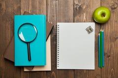 Σωρός των βιβλίων, μήλο, πιό magnifier και κενός στο ξύλο Στοκ Εικόνες