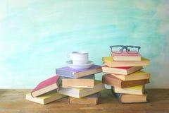 Σωρός των βιβλίων με τα θεάματα και το φλιτζάνι του καφέ Στοκ Φωτογραφία