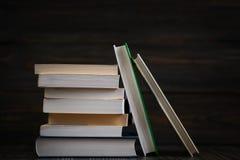 Σωρός των βιβλίων με το σκοτεινό ξύλινο υπόβαθρο Στοκ εικόνα με δικαίωμα ελεύθερης χρήσης
