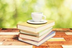 Σωρός των βιβλίων σε έναν εκλεκτής ποιότητας ξύλινο πίνακα με το φλιτζάνι του καφέ στο ν Στοκ Φωτογραφία
