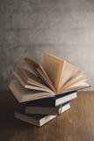 Σωρός των βιβλίων σε έναν ξύλινο πίνακα και στον γκρίζο συμπαγή τοίχο backg Στοκ Φωτογραφία
