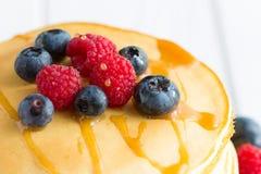 Σωρός των γλυκών τηγανιτών με το φρέσκο σιρόπι βακκινίων, σμέουρων, της Apple και σφενδάμνου στο άσπρο ελαφρύ υπόβαθρο στοκ φωτογραφίες με δικαίωμα ελεύθερης χρήσης