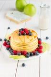 Σωρός των γλυκών τηγανιτών με το φρέσκο σιρόπι βακκινίων, σμέουρων, της Apple και σφενδάμνου στο άσπρο ελαφρύ υπόβαθρο στοκ εικόνες