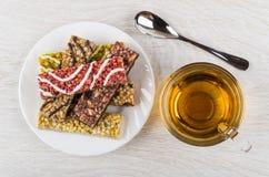 Σωρός των διαφορετικών φραγμών granola στο πιάτο, κουταλάκι του γλυκού, φλυτζάνι του τσαγιού Στοκ Φωτογραφία