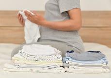 Σωρός των ενδυμάτων και της εγκύου γυναίκας μωρών σε ένα κρεβάτι στοκ φωτογραφία με δικαίωμα ελεύθερης χρήσης
