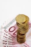 Σωρός των ευρο- νομισμάτων στις ευρο- σημειώσεις Στοκ Εικόνες
