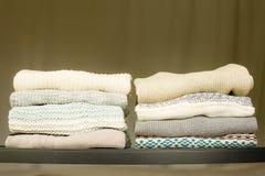 Σωρός των θερμών πουλόβερ σε ένα ράφι στοκ εικόνες