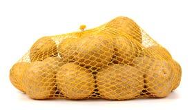 Σωρός των κίτρινων ακατέργαστων potatos στην κόκκινη τσάντα σειράς Στοκ φωτογραφία με δικαίωμα ελεύθερης χρήσης