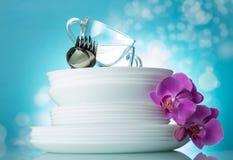Σωρός των καθαρών πιάτων, των φλυτζανιών, των κουταλιών και των δικράνων σε ανοικτό μπλε Στοκ Φωτογραφίες