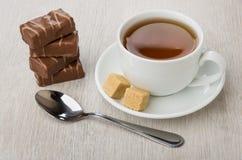 Σωρός των καραμελών σοκολάτας, φλυτζάνι του τσαγιού, ζάχαρη και κουταλάκι του γλυκού Στοκ Εικόνα