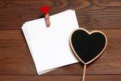 Σωρός των καρτών με το ξύλινο clothespin με την κόκκινη καρδιά και τη μαύρη ξύλινη καρδιά πινάκων κιμωλίας στον ξύλινο πίνακα Στοκ Φωτογραφίες
