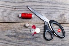 Σωρός των κουμπιών, ψαλίδι, δακτυλήθρα, μασούρι του νήματος Στοκ Φωτογραφία