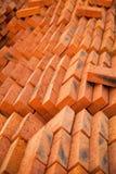 Σωρός των κόκκινων νέων τούβλων που τακτοποιούνται ωραία στο εργοτάξιο οικοδομής Στοκ Φωτογραφίες
