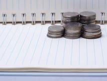 Σωρός των νομισμάτων σε ένα βιβλίο σε ένα ξύλινο γραφείο Έννοια της αποταμίευσης mon Στοκ Εικόνες