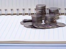 Σωρός των νομισμάτων σε ένα βιβλίο σε ένα ξύλινο γραφείο Έννοια της αποταμίευσης mon Στοκ Φωτογραφία