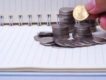 Σωρός των νομισμάτων σε ένα βιβλίο σε ένα ξύλινο γραφείο Έννοια της αποταμίευσης mon Στοκ εικόνες με δικαίωμα ελεύθερης χρήσης