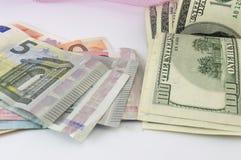 Σωρός των λογαριασμών ευρώ και δολαρίων σε έναν πίνακα Στοκ Φωτογραφίες