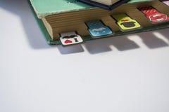 Σωρός των παλαιών βιβλίων με τα γυρισμένα κίτρινα φύλλα σε ένα άσπρο υπόβαθρο Εύθυμοι σελιδοδείκτες με τα moustaches του διαφορετ στοκ εικόνες