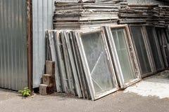 Σωρός των παλαιών ξύλινων πλαισίων παραθύρων με το γυαλί υπαίθρια Σπασμένα υλικά μετά από την ενέργεια παραθύρων - βελτίωση τεχνο στοκ εικόνες με δικαίωμα ελεύθερης χρήσης