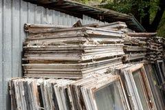 Σωρός των παλαιών ξύλινων πλαισίων παραθύρων με το γυαλί υπαίθρια Σπασμένα υλικά μετά από την ενέργεια παραθύρων - βελτίωση τεχνο στοκ φωτογραφία