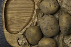 Σωρός των πατατών που βρίσκονται στους ξύλινους πίνακες με μια τσάντα πατατών Στοκ Φωτογραφίες