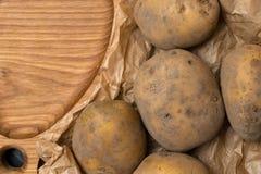 Σωρός των πατατών που βρίσκονται στους ξύλινους πίνακες με μια τσάντα πατατών Στοκ εικόνες με δικαίωμα ελεύθερης χρήσης